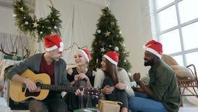 Een vrolijk bedrijf van jonge vrienden in hoeden van Santa Claus die pretzitting op de vloer voordien van een Kerstboom hebben stock footage