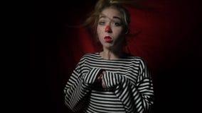 Een vrolijk blonde in de clown` s onverbiddelijke draaien en de pogingen om haar haar van haar neus weg te blazen stock videobeelden