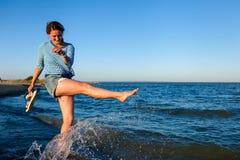 Een vrolijk donkerharige in het gekleurde draad en denimjasje glimlacht, loopt langs het strand en geniet van de heldere zon op a stock fotografie