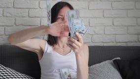 Een vrolijk glimlachend jong meisje zit op de laag en werpt op dollars Concepten goede geluk en winsten, motivatie langzaam stock footage