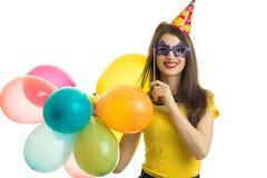 Een vrolijk jong meisje in een gele blouse die grote gekleurde ballen en kunstmatige oogglazen houden Royalty-vrije Stock Afbeeldingen