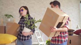 Een vrolijk jong paar gaat een nieuw huis in, danst en heeft pret met dozen in hun handen stock videobeelden