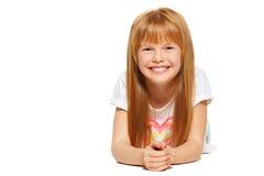 Een vrolijk meisje met rood haar ligt; geïsoleerd op de witte achtergrond stock foto's