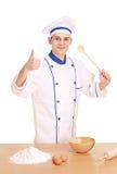 Een vrolijke chef-kok die met omhoog duimen voorbereidingen treft te koken Stock Foto