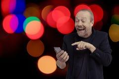 Een vrolijke, gebaarde, witte mens spreekt op de telefoon Stock Fotografie