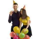 Een vrolijke jonge meisje en het glimlachen kerel met kegels op hun hoofden viert een verjaardag en draagt veel gekleurd Royalty-vrije Stock Afbeeldingen