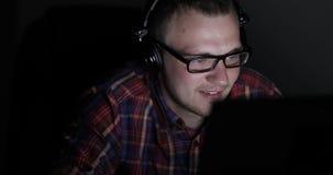 Een vrolijke jonge mens in hoofdtelefoons luistert aan muziekzitting bij de computer stock video