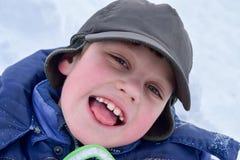 Een vrolijke jongen in een een de winterhoed en jasje glimlacht en onderzoekt de camera Royalty-vrije Stock Fotografie