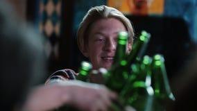 Een vrolijke kerel in het bedrijf van vrienden drinkt bier in een restaurant stock video