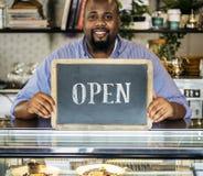 Een vrolijke kleine bedrijfseigenaar met open teken stock fotografie
