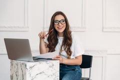 Een vrolijke leuke student schrijft haar rapport terwijl het zitten bij haar laptop en lacht met haar klasgenoten Het Meisje is stock foto's