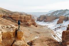 Een vrolijke reiziger met een camera bevindt zich op de rand van de klip in de Charyn-canion in Kazachstan Royalty-vrije Stock Foto