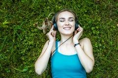 Een vrolijke student die aan muziek op hoofdtelefoons luisteren Park Conce Royalty-vrije Stock Foto