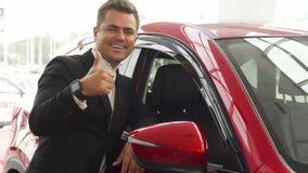 Een vrolijke verkoper richt aan de uitstekende kwaliteit van de auto royalty-vrije stock afbeelding