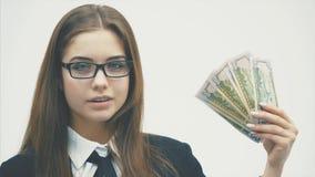 Een vrolijke verraste bedrijfsvrouw die een camera bekijken terwijl het houden van dollars in haar die hand, over een wit wordt g stock video