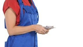 Een vrouw in arbeiders kleedt tellingengeld op witte achtergrond stock fotografie