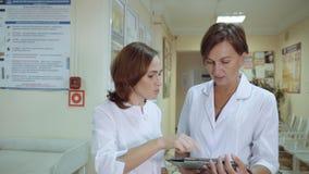 Een vrouw arts loopt onderaan de gang van de polikliniek De arts vangt de belangrijkste arts lopend langs de gang stock videobeelden