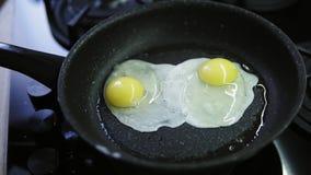Een vrouw barst verse eieren in een pan met heet, sissend boter Recent ontbijt na douche Gezouten, het voorbereidingen treffen stock footage
