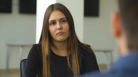 Een vrouw beantwoordt vragen van de werkgever bij het gesprek