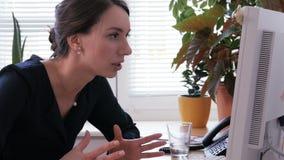 Een vrouw bekijkt boos het computerscherm en vermindert haar hoofd op het toetsenbord stock footage