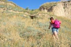 Een vrouw beklimt de heuvel royalty-vrije stock afbeelding