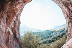 Een vrouw beklimt de rots Stock Afbeeldingen
