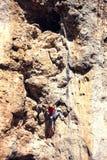 Een vrouw beklimt de rots stock fotografie