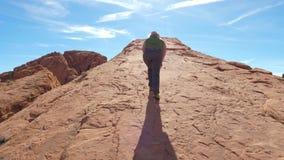 Een Vrouw beklimt op de Berg op de Monolithische Rode Rots stock videobeelden