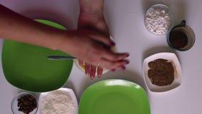 Een vrouw bereidt snoepjes van condens, kokosnotenspaanders en amandelen voor stock video
