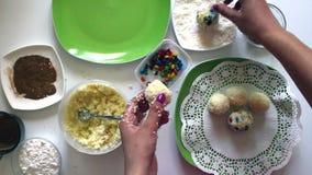 Een vrouw bereidt snoepjes van condens, kokosnotenspaanders en amandelen voor Verfraait snoepjes met gekleurde glans stock video