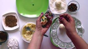 Een vrouw bereidt snoepjes van condens, kokosnotenspaanders en amandelen voor Verfraait snoepjes met gekleurde glans stock footage