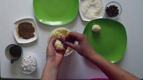 Een vrouw bereidt snoepjes van condens, kokosnotenspaanders en amandelen voor Zij rolt een bal in haar handen, binnen zet amandel stock footage