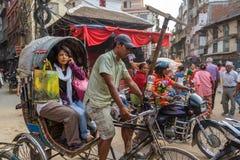 Een vrouw berijdt een riksja door Katmandu, Nepal Stock Foto