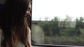 Een vrouw berijdt in een trein en kijkt uit het venster stock video