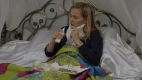 Een vrouw bespat een geneeskunde in de neus Neus Nevel het meisje ligt in een bed met een warme sjaal rond zijn hals Langzame Mot stock footage