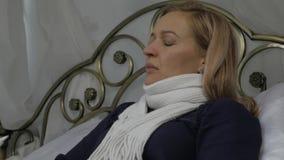Een vrouw bespat een geneeskunde in de neus Neus Nevel het meisje ligt in een bed met een warme sjaal rond zijn hals Langzame Mot stock video
