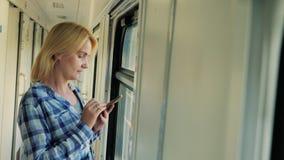 Een vrouw bevindt zich door het venster in de gang van een auto van de passagiersspoorweg Gebruikt een mobiele telefoon stock videobeelden