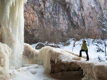 Een vrouw bevindt zich op het ijs dichtbij een waterval Stock Foto's