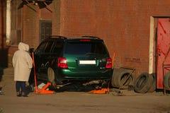 Een vrouw bevindt zich voor een opgekrikte auto met verwijderde wielen royalty-vrije stock foto's