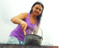 Een vrouw beweegt een soep met een houten lepel in een ketel op de brand algemeen plan stock video