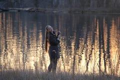 Een vrouw bij de rivierbank in de schemer Stock Fotografie