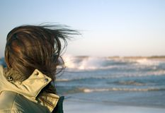 Een vrouw bij een zeer winderige overzees stock foto