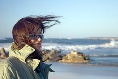 Een vrouw bij een zeer winderige overzees Stock Foto's