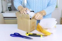 Een vrouw in blauwe trui opent een pakket, pakt een doos met schaar en mes uit royalty-vrije stock foto's