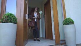 Een vrouw in bruine kleren bevindt zich in de deuropening stock footage