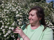 Een vrouw controleert de groei van decoratieve struiken Stock Foto