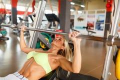Een vrouw in de gymnastiek leidt met een barbell op royalty-vrije stock foto