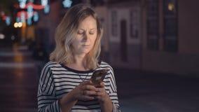 Een vrouw in de straat van een nachtstad communiceert in een boodschapper met een elektronisch apparaat stock video