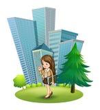Een vrouw dichtbij de pijnboomboom over de lange gebouwen Stock Afbeeldingen