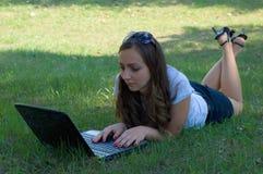 Een vrouw die aan haar notitieboekje werkt Stock Afbeelding